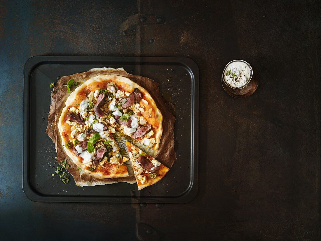 Lamb pizza with feta cheese and mint yoghurt on a dark brown surface