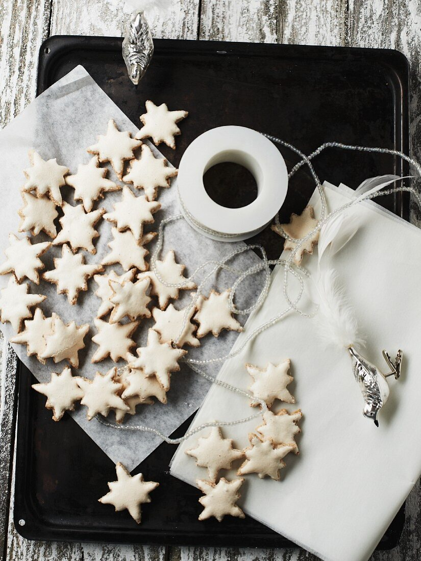 Cinnamon stars on a baking tray with silver bird figures