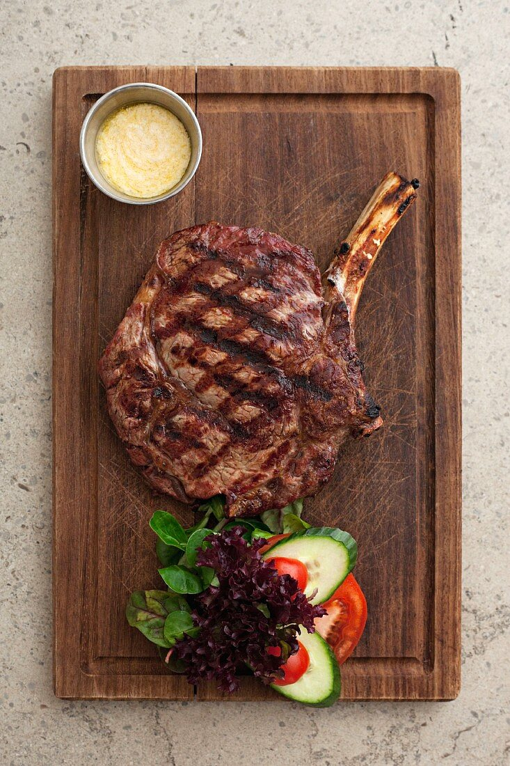A grilled beef chop on a wooden board (seen from above)