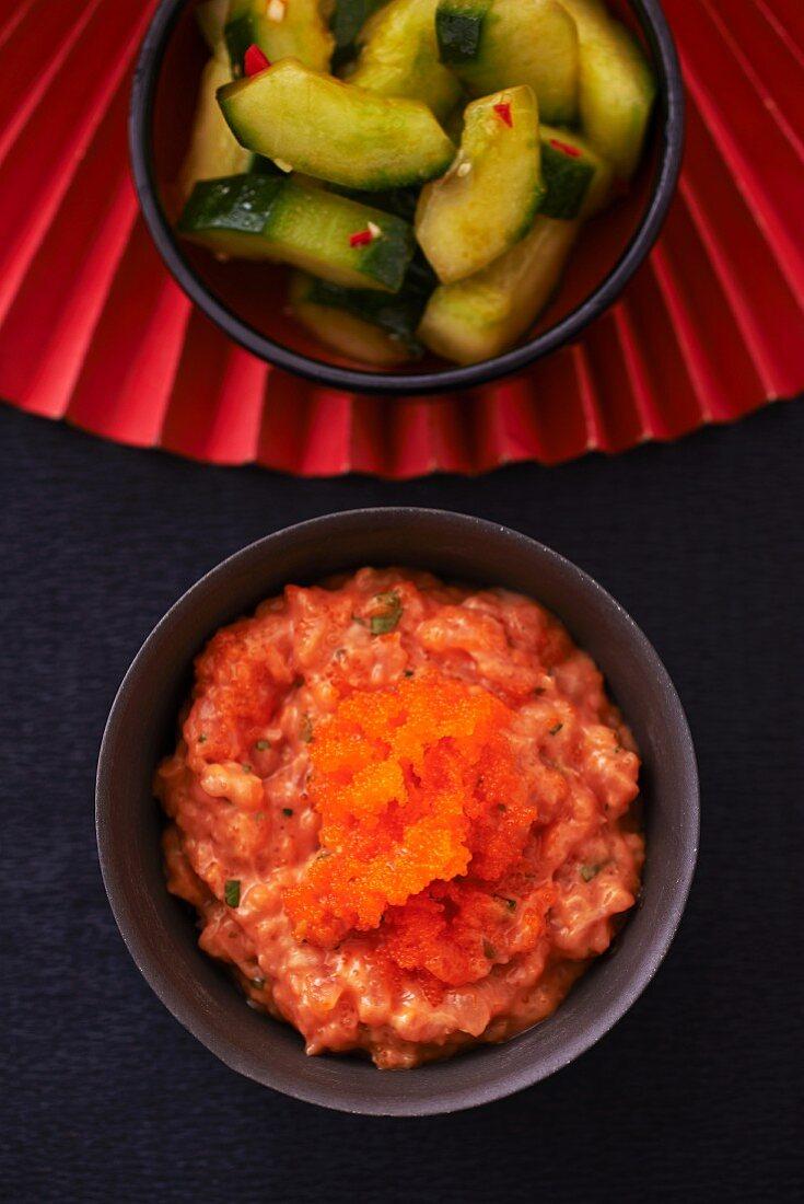 Salmon tartar with orange caviar and a spicy cucumber salad