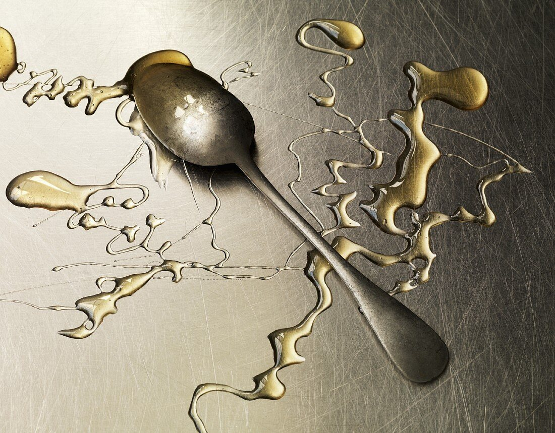 Honey and a spoon on a metal surface