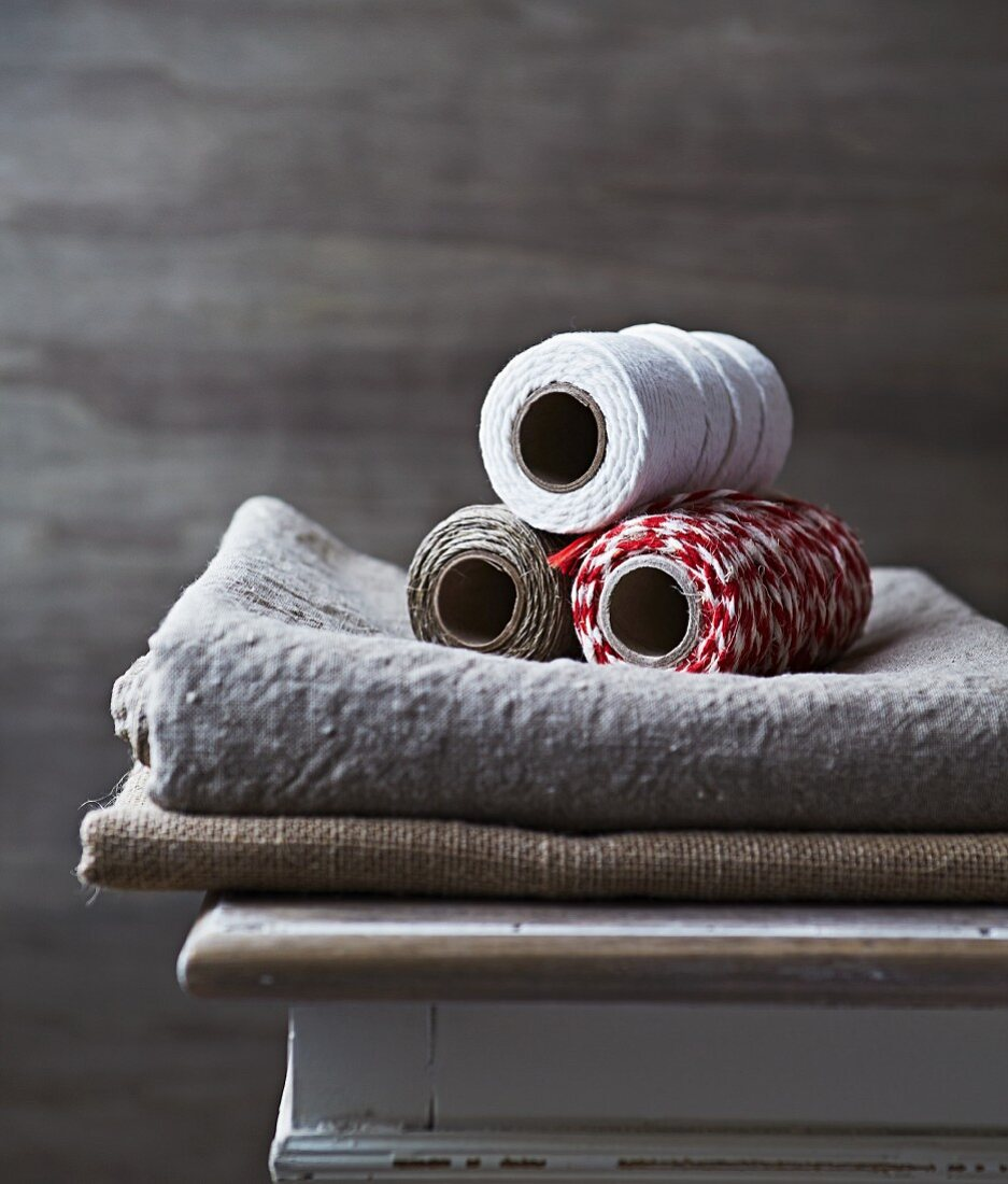 Three spools of kitchen twine on linen cloth