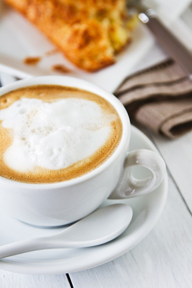 A cappuccino with milk foam and an apple turnover in the background