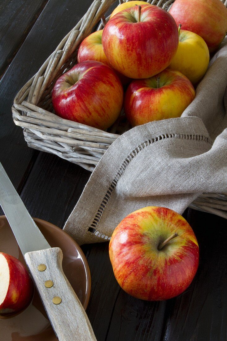 Apples in a rectangular basket with a linen serviette, one apple next to the basket