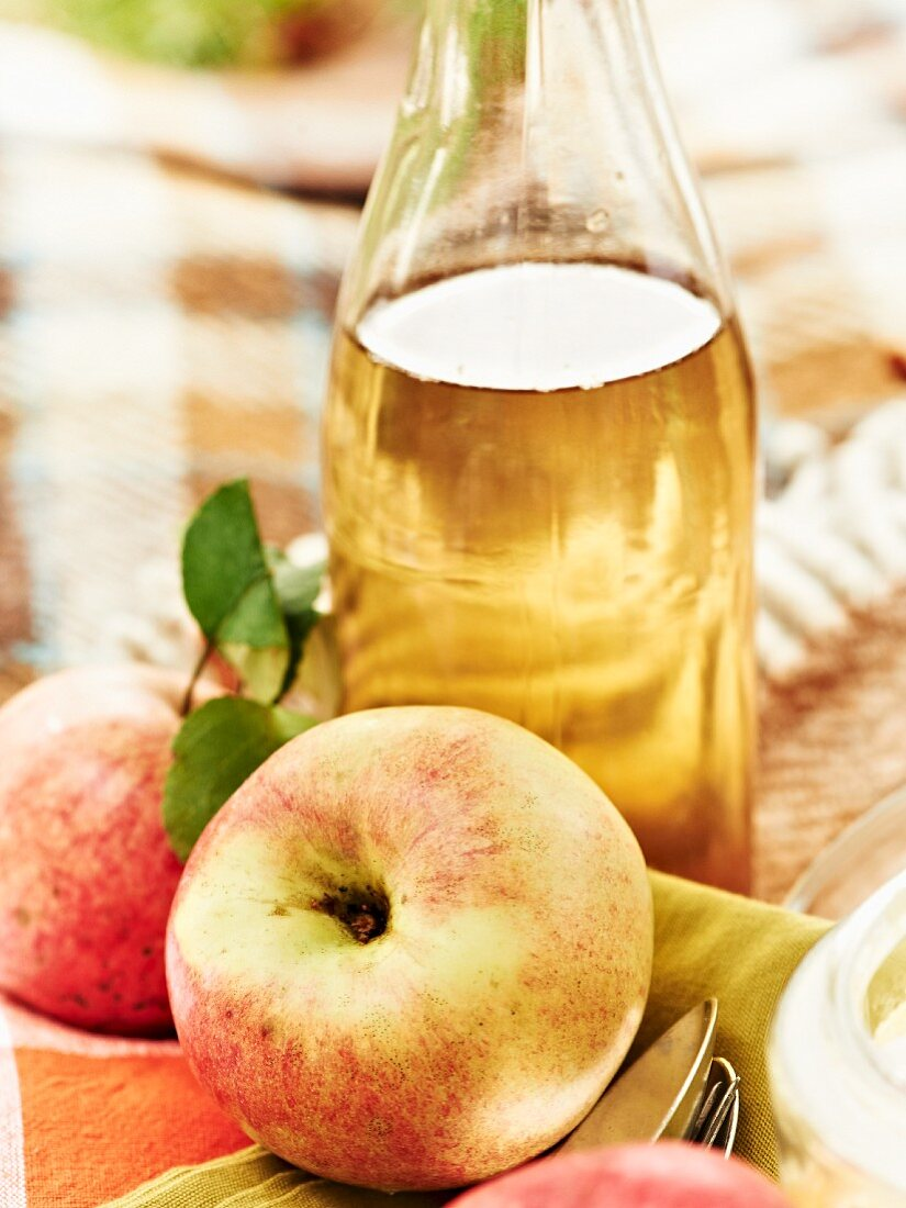 A bottle of apple juice and fresh apples at an autumnal picnic
