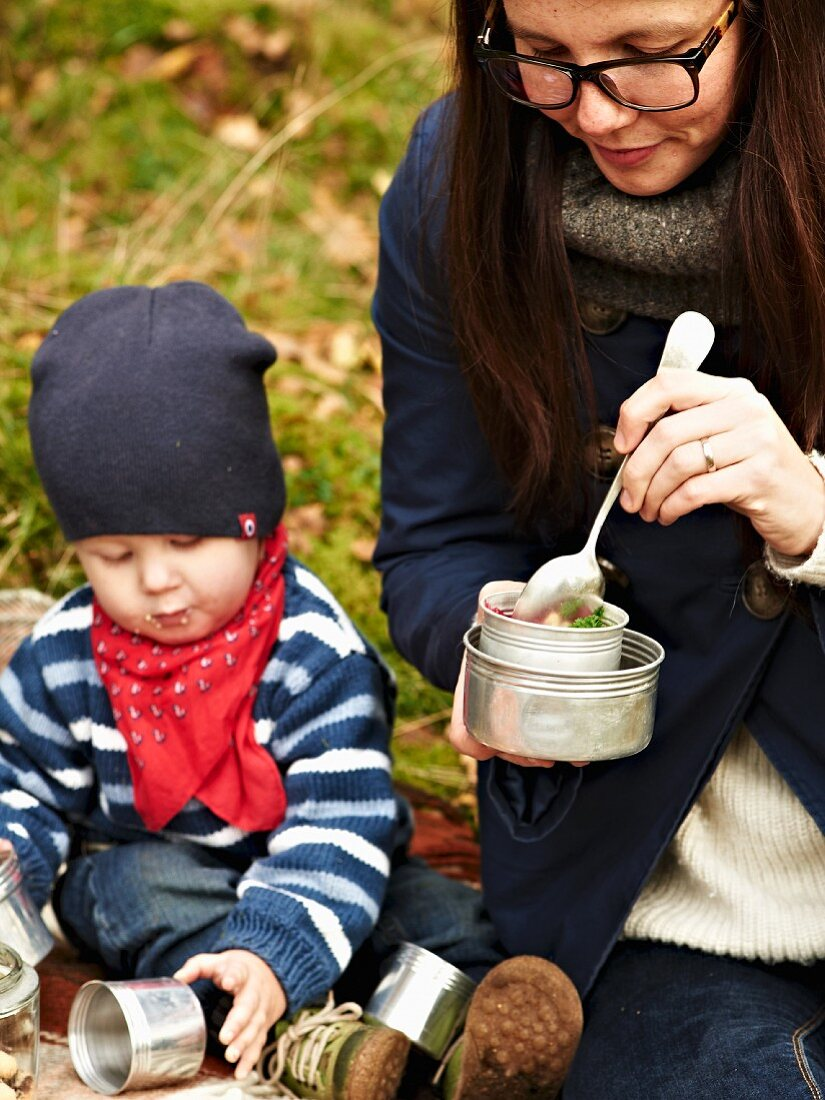 A woman and a child eating beetroot soup at an autumnal picnic