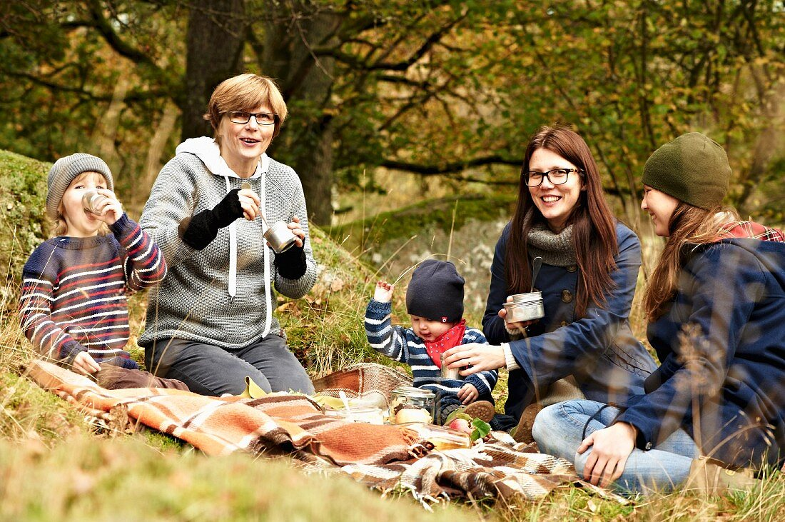 Women and children having an autumnal picnic in a forest