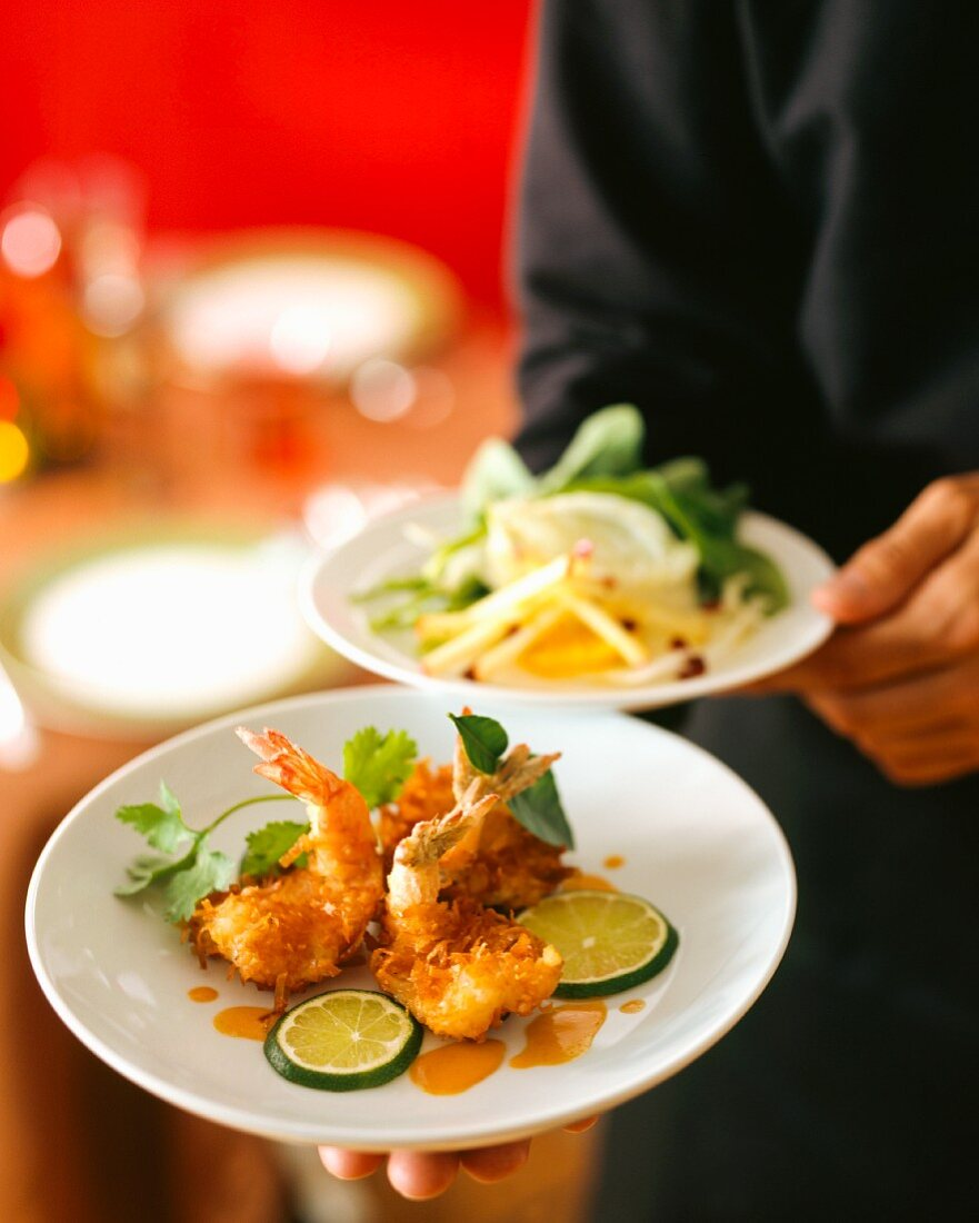 A waiter serving coconut prawns with limes