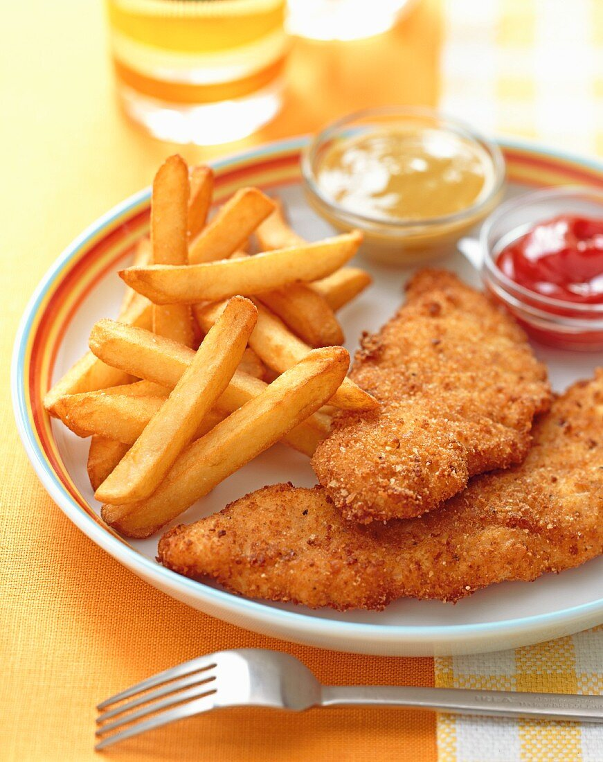 Breaded chicken fillets served with fries, honey-mustard and ketchup