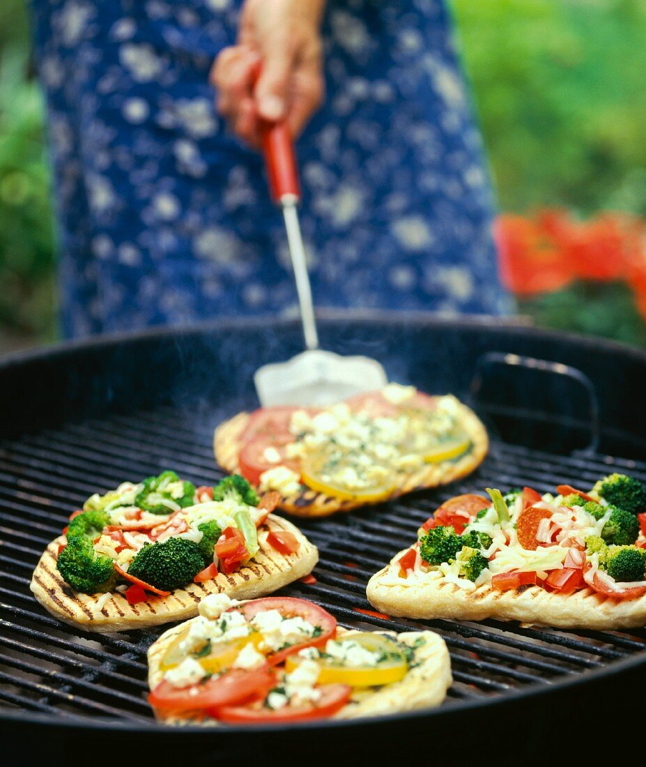 Pita bread pizzas being cooked on a barbecue