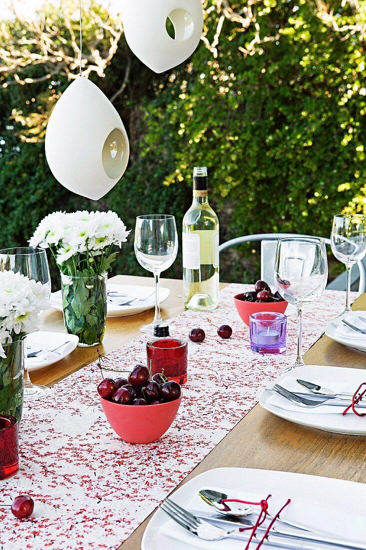 Bowls of fruit on set garden table below white lanterns