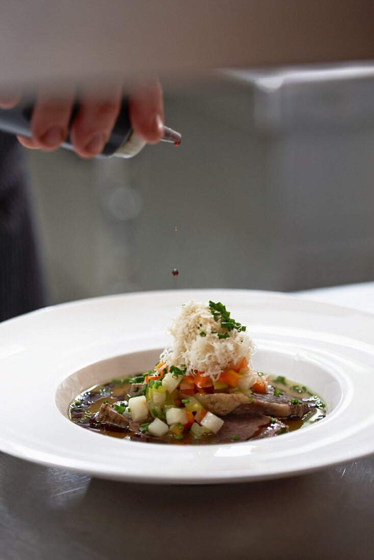 Prime boiled beef in broth being drizzled with balsamic vinegar