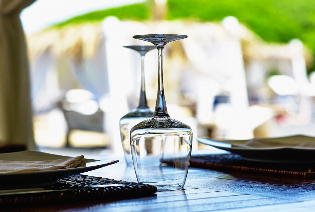 A place setting a upside-down wine glasses on a table in a restaurant