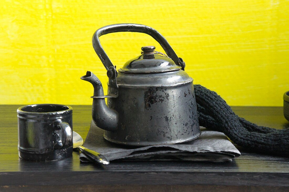 An old coffee pot and a coffee cup