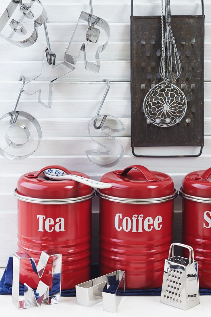 Arrangement of red tea and coffee storage jars, letter-shaped pastry cutters and grater in kitchen