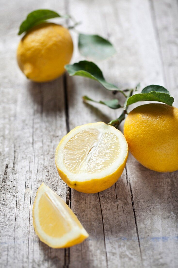 Lemons (whole, halved and a wedge) with leaves on a wooden surface