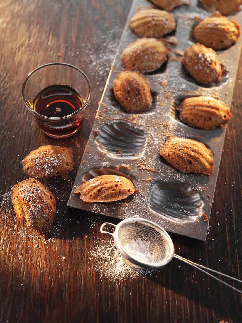Madeleines with icing sugar in a baking tin