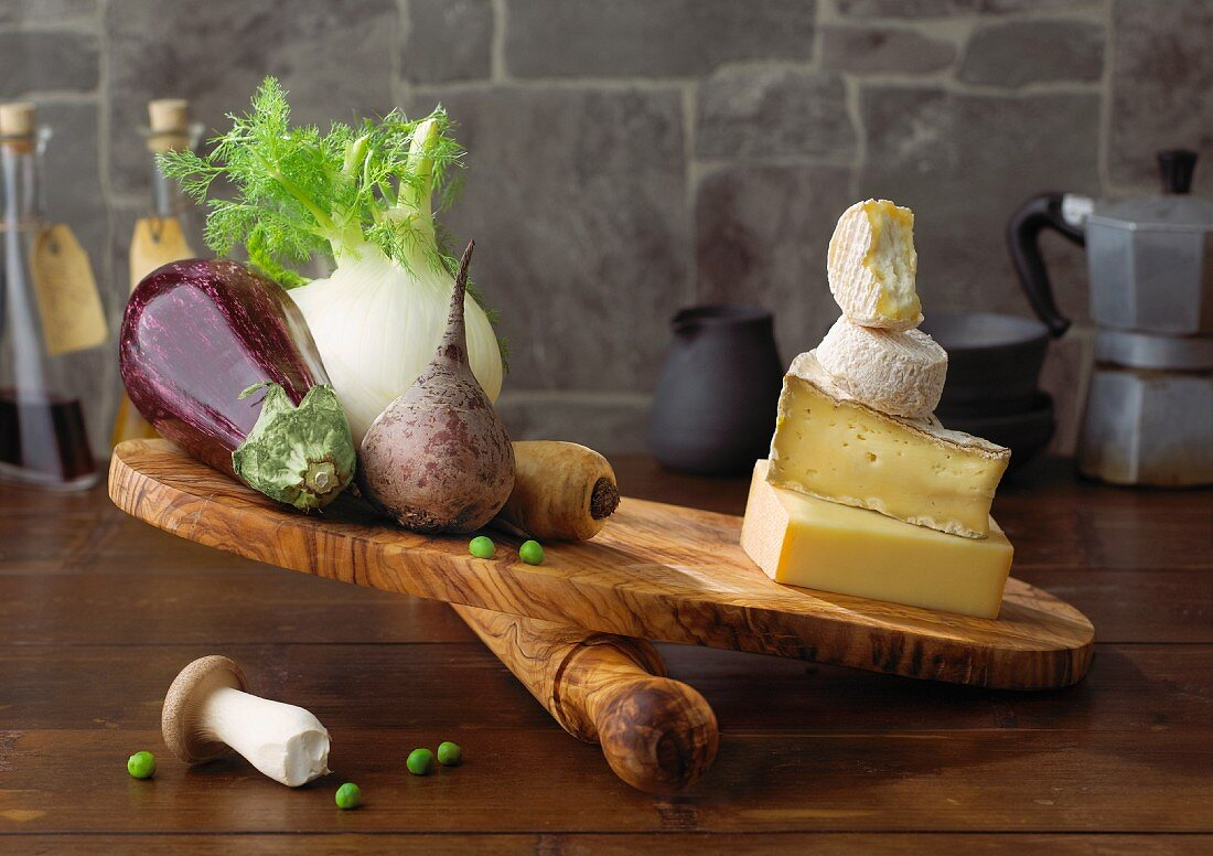 Vegetables and cheese being compared on a chopping board