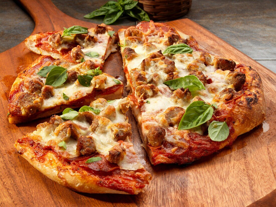 A rustic pizza with sausage, cheese and basil