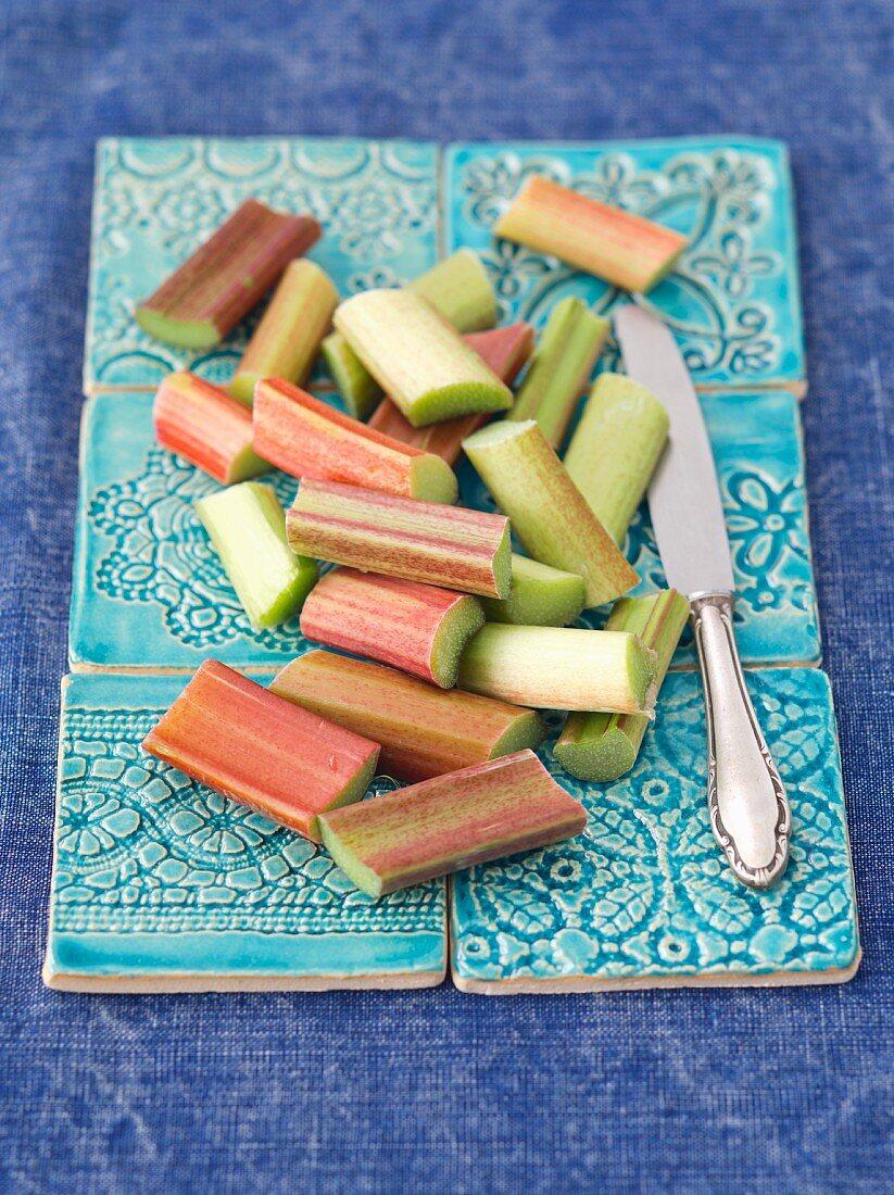Sliced rhubarb on pastel-blue ceramic tiles