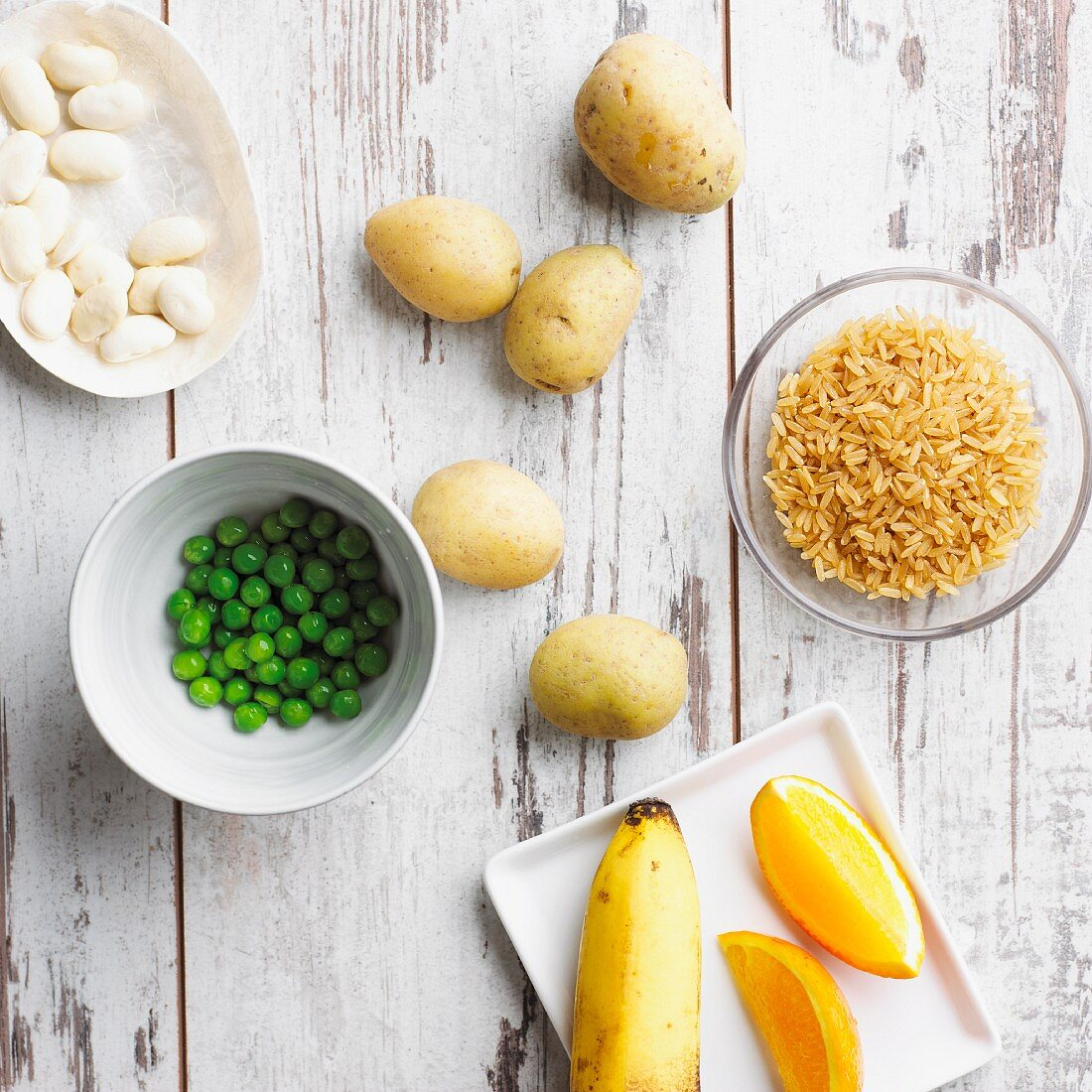 An arrangement of peas, potatoes, rice, beans, banana and orange (good carbohydrates)