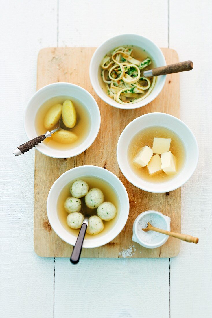 Various soup ingredients in bowls of stock