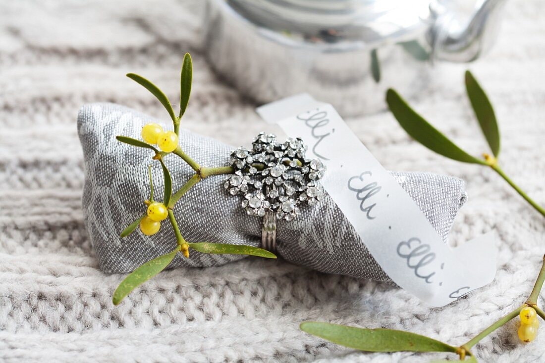 A linen napkin decorated with a sprig of mistletoe and a ring with a transparent paper strip as a name tag