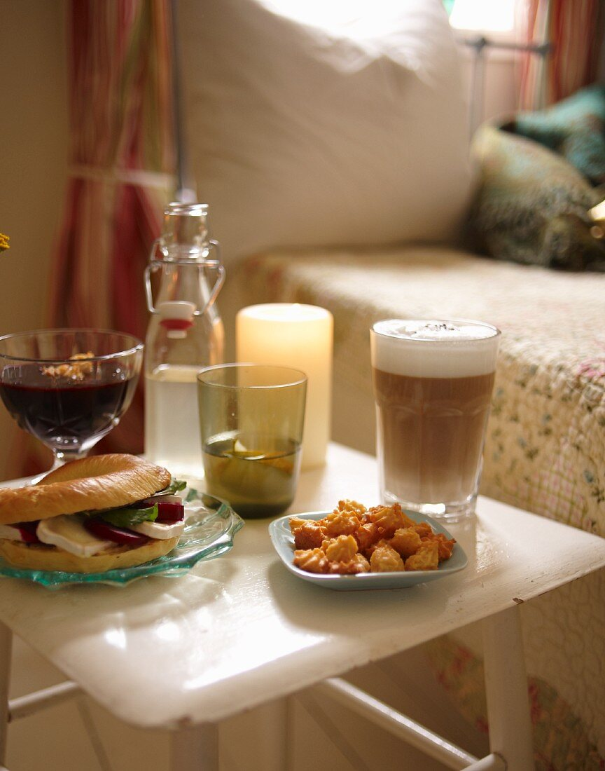An autumnal breakfast featuring a bagel, almond biscuits, blueberry soup and coffee in a bedroom