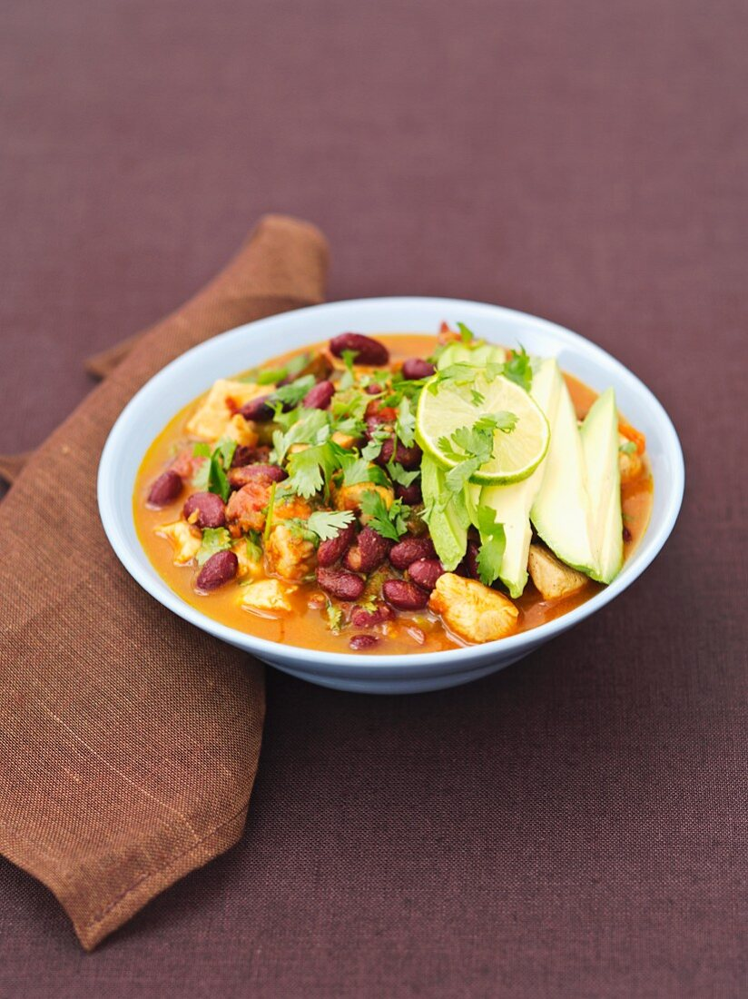 Chicken with chipotle and kidney beans in tomato sauce with coriander, lime and avocado