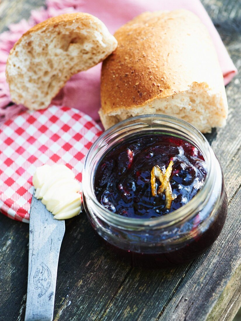 Blueberry and orange marmalade in a screw-top jar with butter and bread rolls