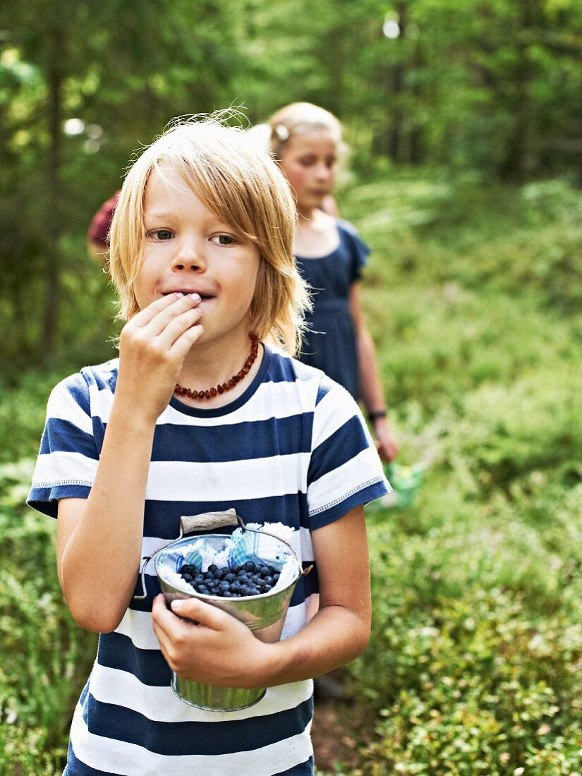 A little boy in a forest eating freshly picked blueberries with a little girl in the background