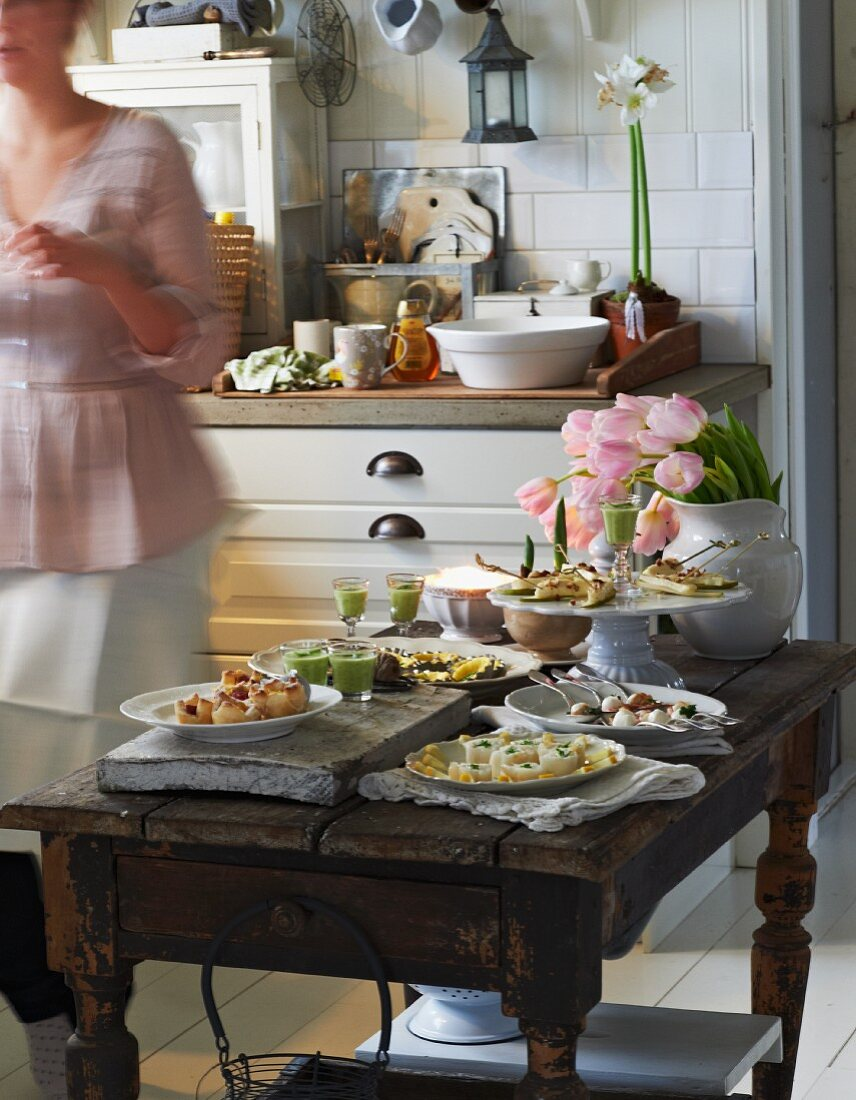 A festive buffet with various canapés on a rustic wooden table in a cosy country house-style kitchen