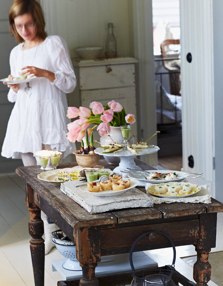 A festive buffet with various canapés and a bunch of tulips on a rustic wooden table with a young woman eating in the background