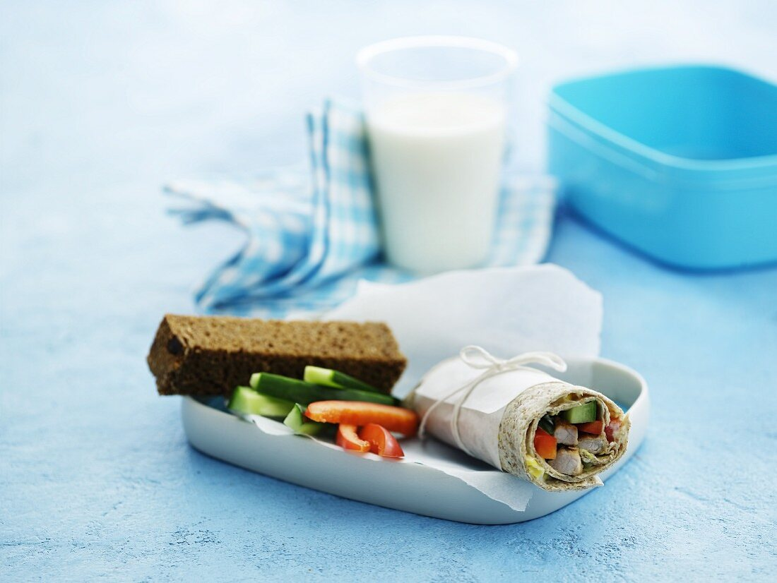 A wrap, vegetables sticks, bread and milk for lunch