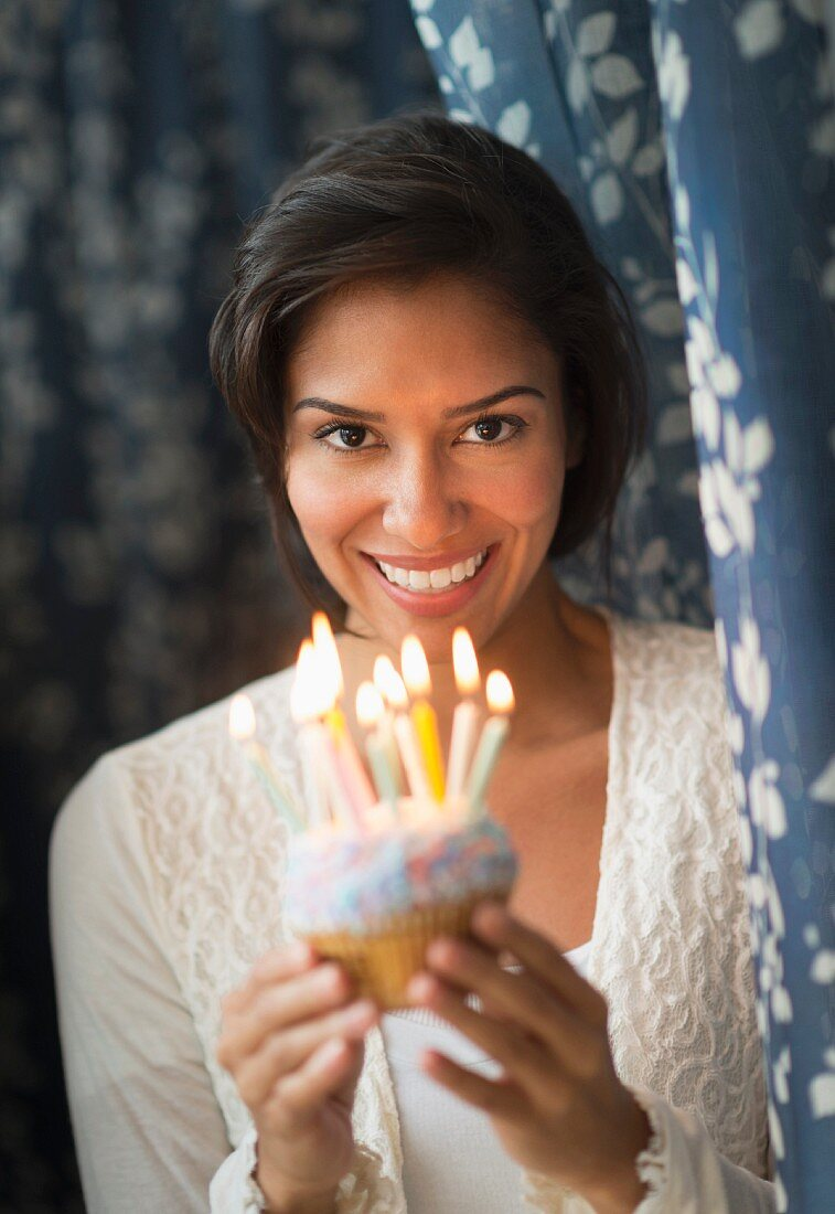 A dark haired woman holding a birthday cake with candles
