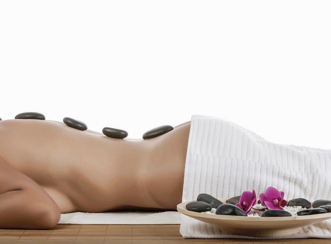 A woman having a 'La Stone' treatment (medicinal treatment using stones)