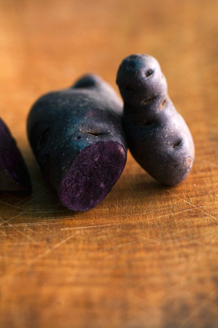Purple potatoes on a wooden surface