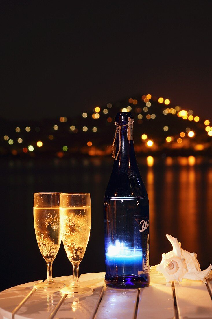 Nighttime atmosphere with two glasses and bottle of sparkling wine on table by the sea