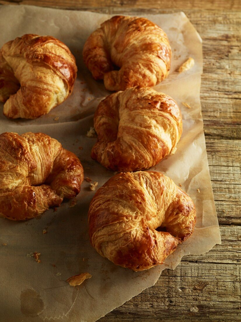 Croissants on a piece of baking paper on a wooden surface