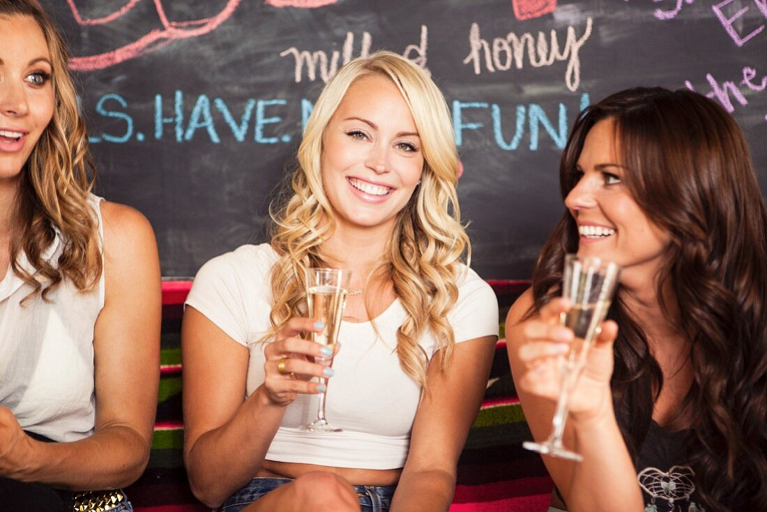 Young women drinking champagne in a bar