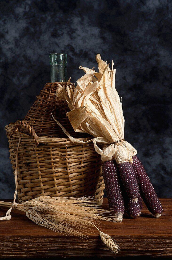 Corn cobs, ears of wheat and a demijohn