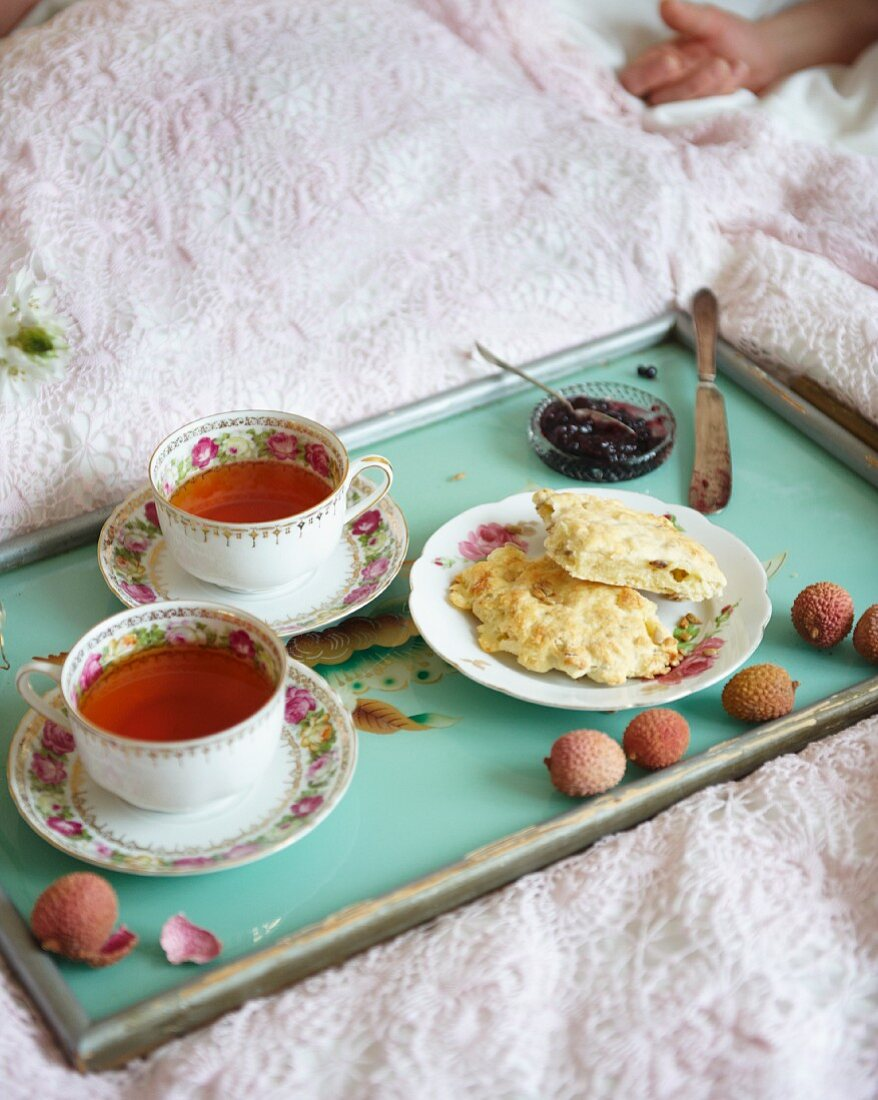 Breakfast in bed with spiced tea and sunflower seed and cheese scones with blueberry jam
