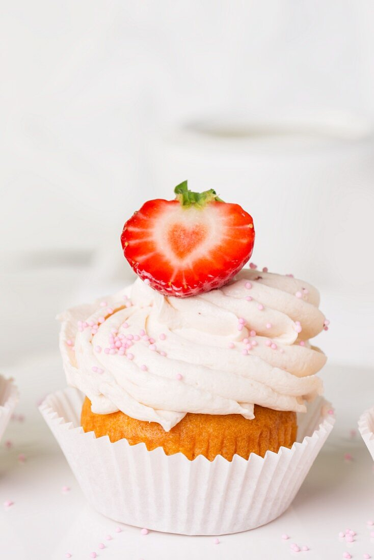 A strawberry cupcake decorated with pink sugar pearls