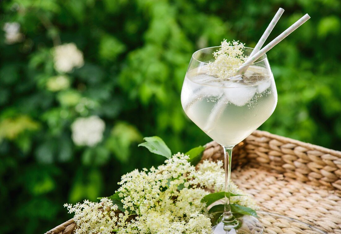 And elderflower cocktail on a cork tray in a garden