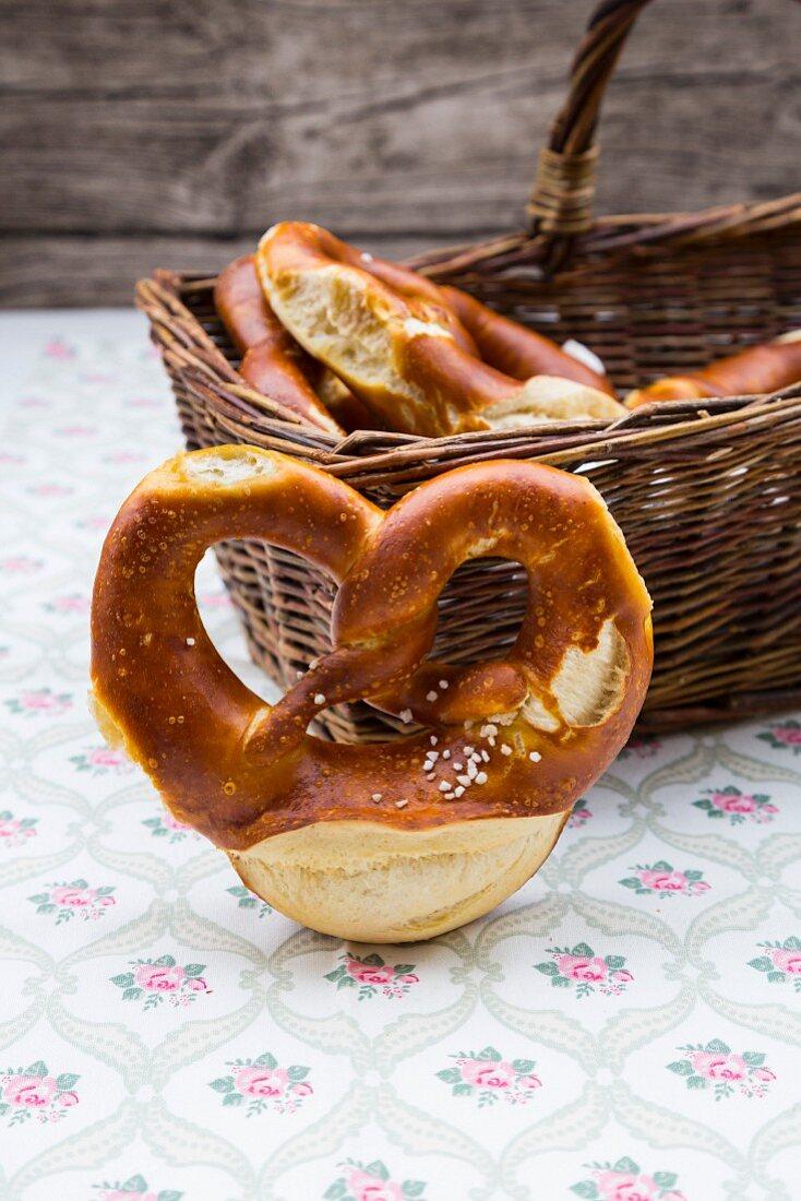 A basket of salted pretzels on a floral patterned tablecloth