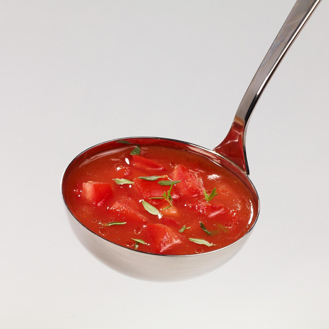 Tomato soup with thyme in a ladle
