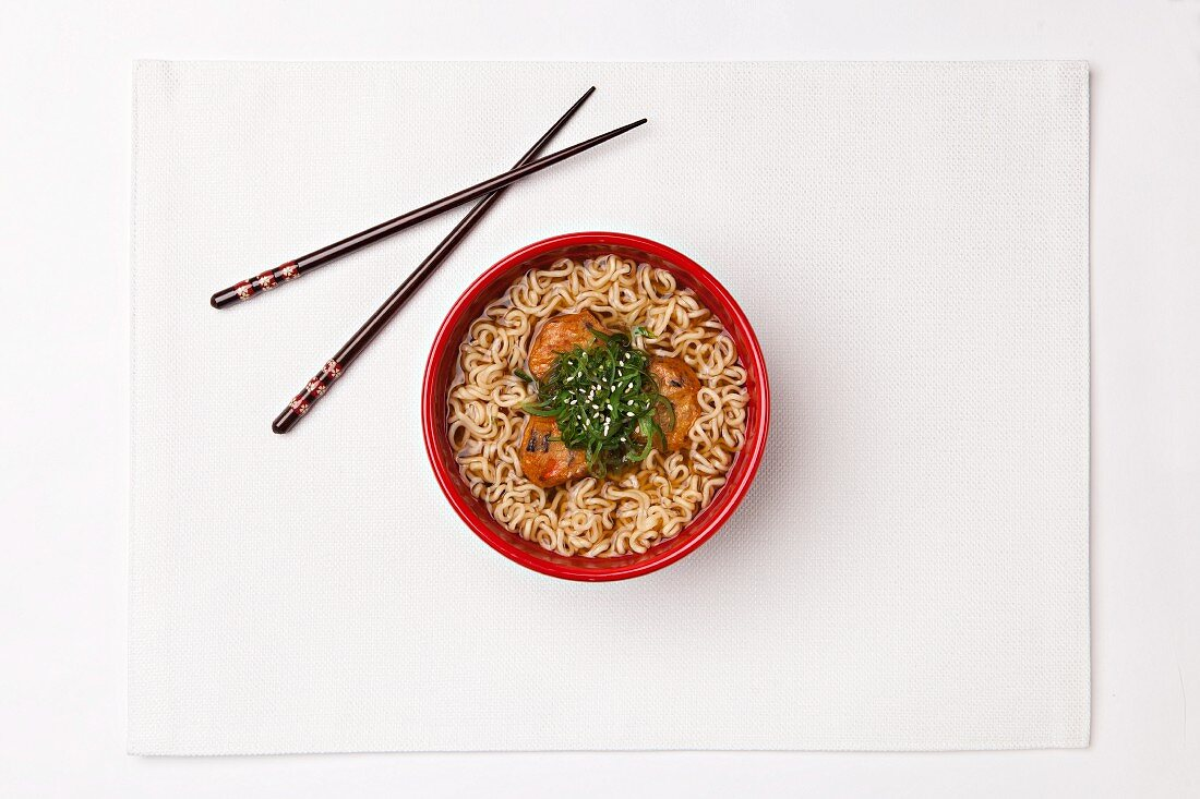 Wheat noodle soup with carrots, spring onions, pepper and sesame seeds (Japan)