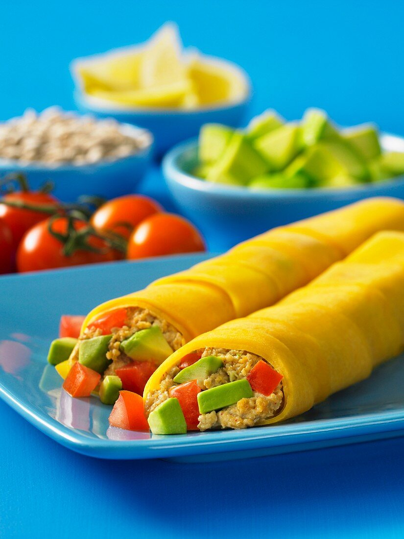 Burritos filled with tuna, avocado and tomatoes