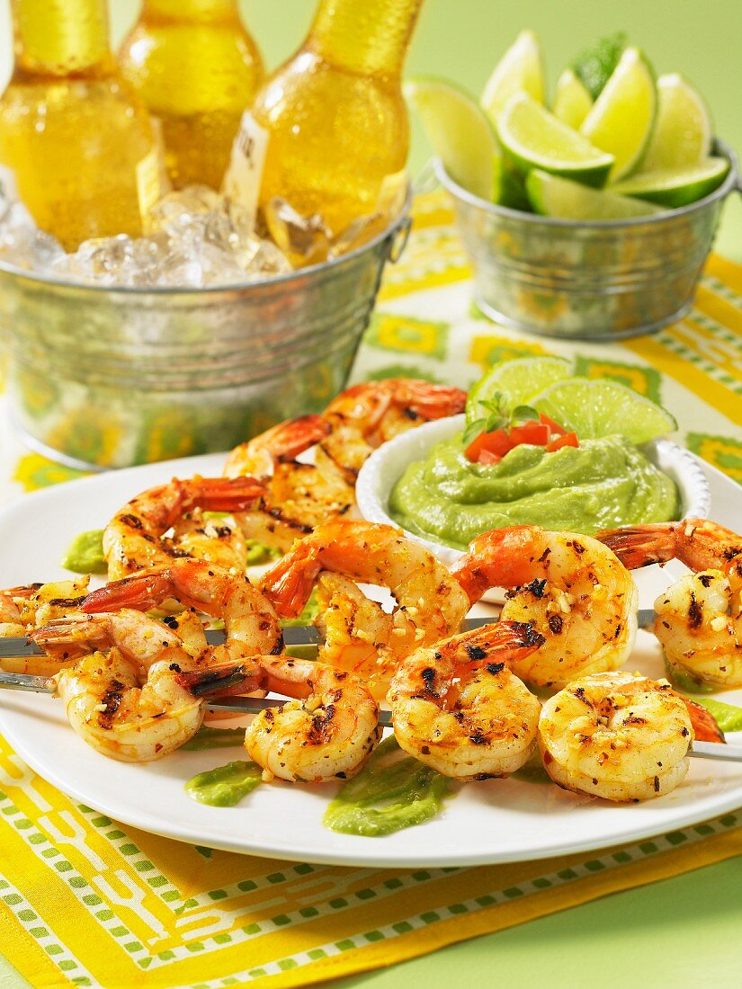 Grilled shrimp skewers, a bowl of avocado cream and beer in an ice bucket