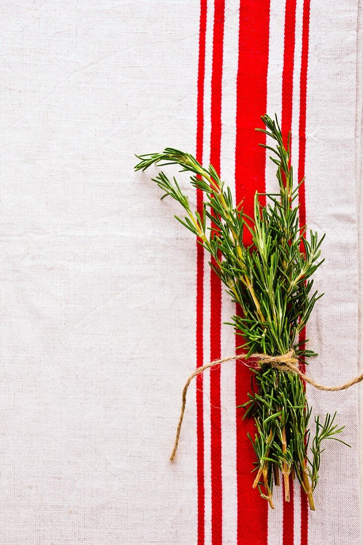 A bunch of rosemary on a red and white tea towel